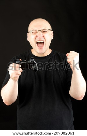middle age man wearing glasses and black tshirt playing video game holding game controller against black background  - stock photo