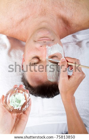 middle age man with facial mask in beauty salon - stock photo