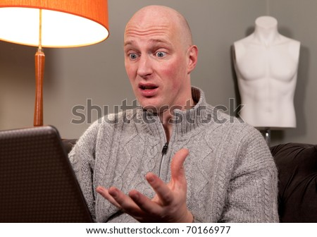 middle age man with laptop computer working from home. male in domestic environment, sitting room or lounge, in the evening - stock photo