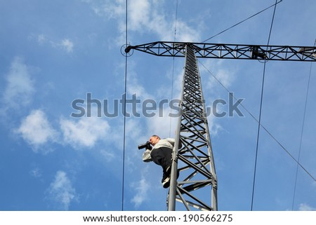 Middle age photographer taking picture  from high voltage electrical pylon, unusual angle - stock photo