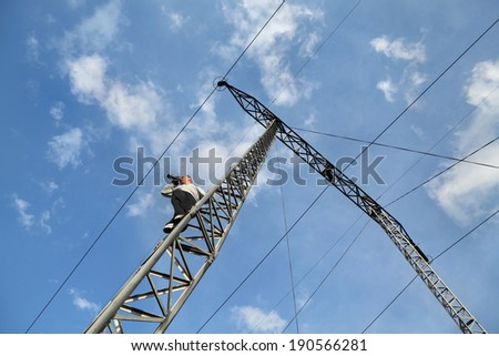 Middle age photographer taking picture  from high voltage electrical pylon, unusual angle