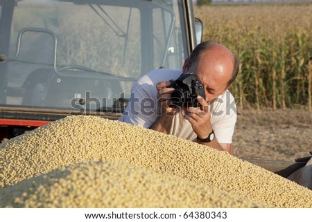 Middle age photographer taking picture of soy at trailer - stock photo