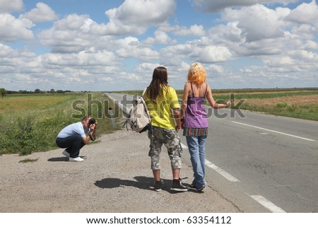 Middle age photographer taking picture of young hiking couple - stock photo