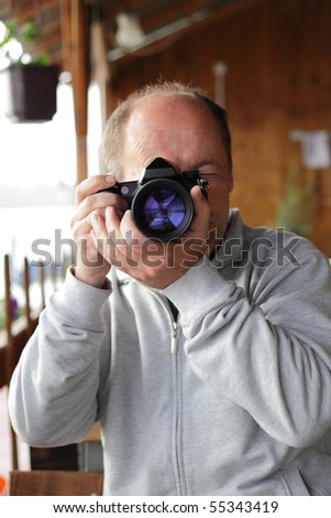 Middle age photographer taking picture with his digital camera