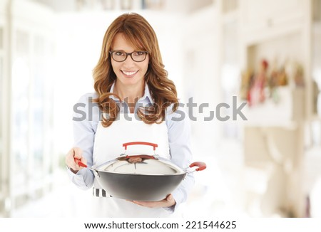 Middle age restaurant owner standing at kitchen, while holding pan in hands. Small business.  - stock photo