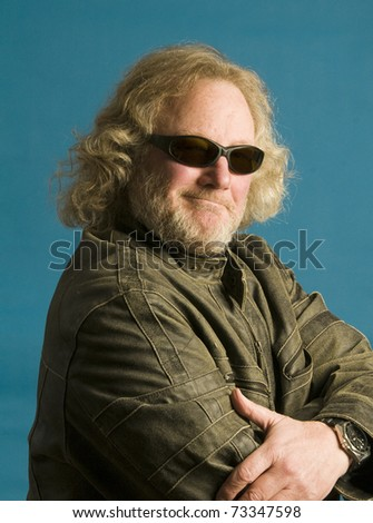 middle age senior biker man long hair and beard wearing leather jacket sunglasses and happy with a confident smile - stock photo