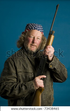 middle age senior long hair wearing leather jacket American flag bandanna angry protective holding rifle firearm - stock photo