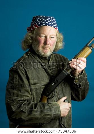 middle age senior long hair wearing leather jacket American flag bandanna  holding rifle firearm - stock photo