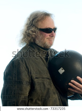 middle age senior long hair wearing leather jacket holding motorcycle helmet and smiling - stock photo
