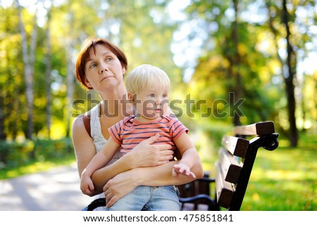 Middle age woman and her cute toddler grandson enjoy sunny autumn day