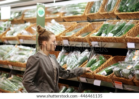 Middle-age woman buying vegetables at the market - stock photo