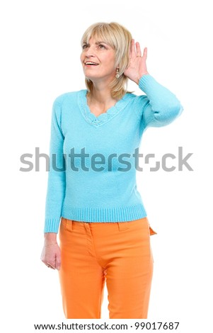 Middle age woman holding hand near ear and trying to hear something