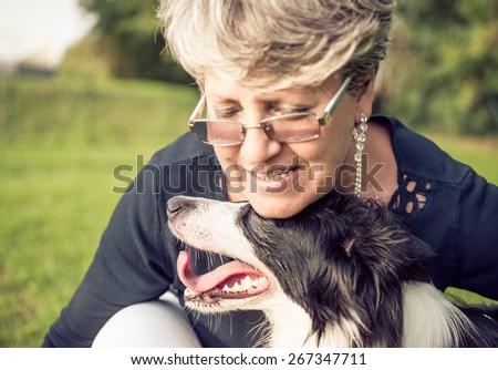middle age woman hugging her border collie. concept about animals and people - stock photo