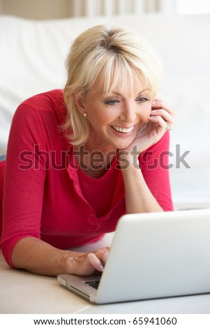 Middle age woman on her laptop computer - stock photo