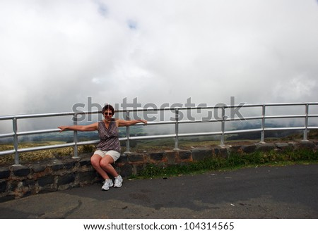 Middle-age Woman Sitting on Foggy Mountaintop Guardrail - stock photo