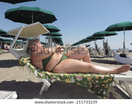 middle age woman sun bathing in bikini - stock photo