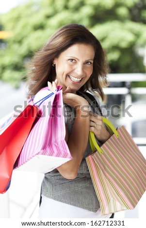 middle age woman with colorful bags