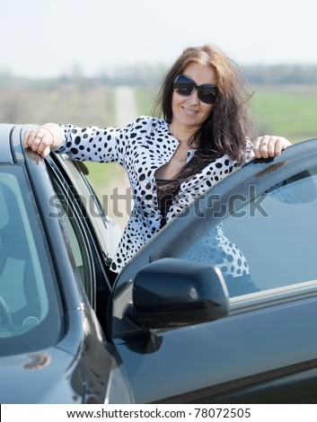 middle age woman with her car at road - stock photo