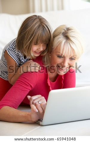 Middle age woman with young girl using laptop computer - stock photo