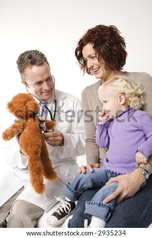 Middle-aged adult Caucasian male doctor holding stethoscope to teddy bear while Caucasian mother and daughter watch. - stock photo