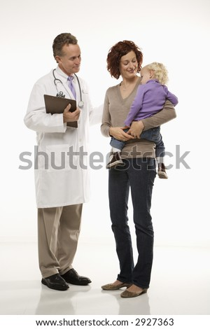 Middle-aged adult Caucasian male doctor introducing himself to mid-adult mother and her daughter. - stock photo