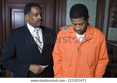 Middle aged advocate consoling male criminal in the courtroom - stock photo