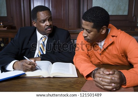 Middle aged advocate sitting with criminal in the courtroom - stock photo