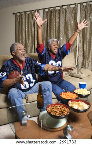 Middle-aged African-American couple cheering and watching football game. - stock photo