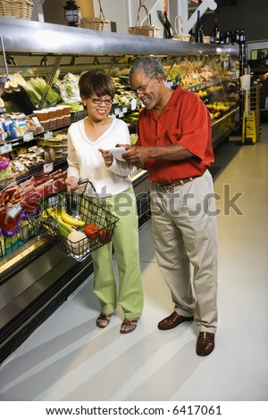Middle aged African American couple in grocery store pointing at shopping list and smiling. - stock photo