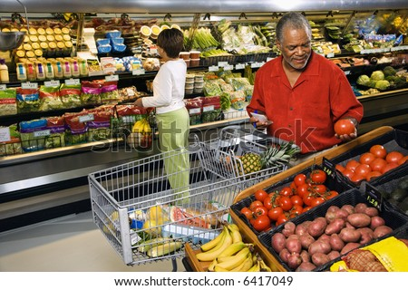 Middle aged African American man and woman in grocery store shopping for produce. - stock photo