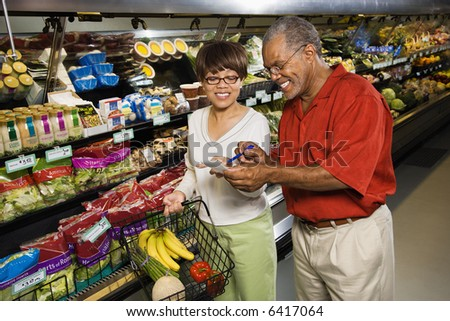 Middle aged African American man and woman in grocery store smiling and pointing at shopping list.
