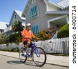Middle aged African American man bicycling down street next to homes and fence. - stock photo