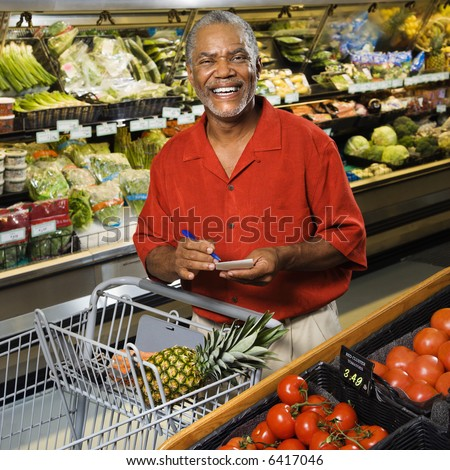 Middle aged African American man in grocery store holding shopping list and smiling at viewer. - stock photo
