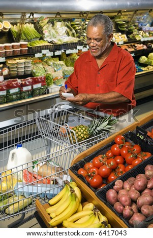 Middle aged African American man in grocery store writing on shopping list. - stock photo
