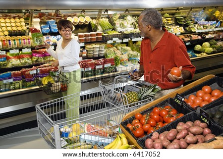 Middle aged African American woman pointing out produce in grocery store to middle aged man. - stock photo