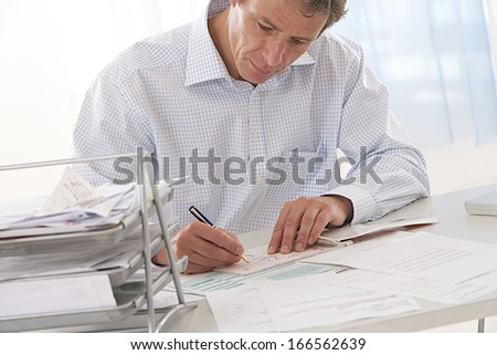 middle aged  and handsome businessman in his office working and looking at finance  - stock photo