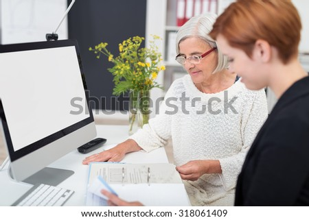 Middle Aged and Young Businesswomen Reading Some Documents at the Table Inside the Office. - stock photo