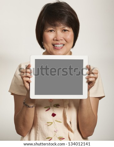 Middle aged Asian woman holding a computer tablet - stock photo