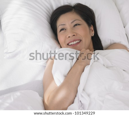 Middle-aged Asian woman laying in bed
