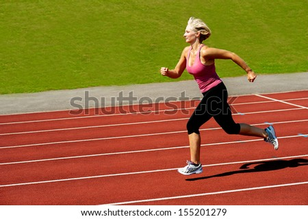 Middle aged athlete running down the track