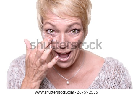 Middle-aged attractive blond woman applying anti-aging cream to the wrinkles around her eyes in an effort to combat aging in a skincare and beauty concept - stock photo