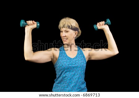 Middle-aged, baby-boomer woman exercising with weights and enjoying it - stock photo