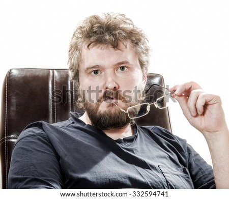 Middle-aged bearded man sits in leather chair thoughtfully holding glasses. - stock photo