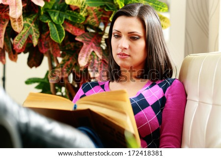 Middle-aged beautiful woman reading the book at home