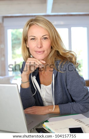 Middle-aged blond woman working at home with laptop - stock photo