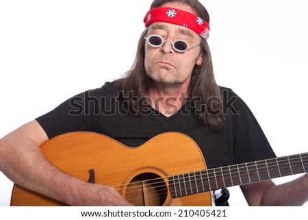 Middle-aged bohemian male artist wearing hippie accessories as headband and small round sunglasses while playing guitar, portrait on white