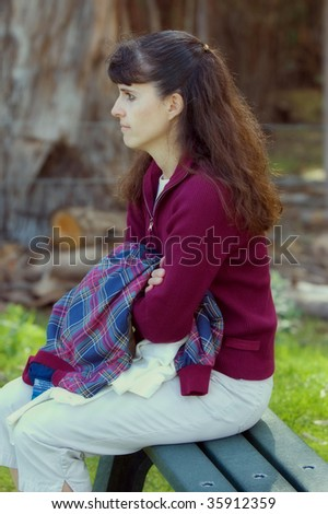 Middle aged brown haired woman sitting on a park bench collecting her thoughts - stock photo