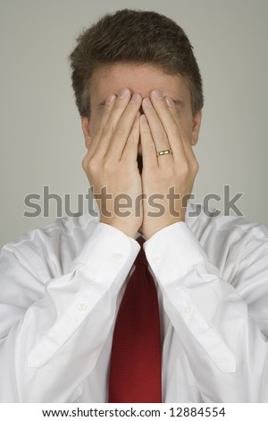 Middle aged business man hiding behind his hands as if he is in trouble - stock photo
