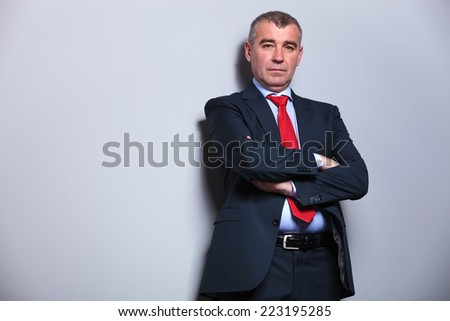 Middle aged business man looking at the camera while holding his arms crossed, against a grey wall. - stock photo