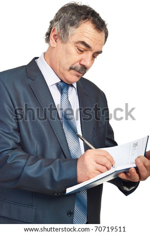 Middle aged business man writing in personal agenda isolated on white background - stock photo